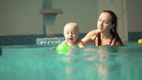 Cute blonde toddler is diving under the water in the swimming pool to get his toy while his mother is teaching him how to swim. An underwater shot