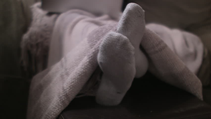 Playful feet with white socks of a female on a couch under a comfy blanket. Medium shot. Shallow depth of field