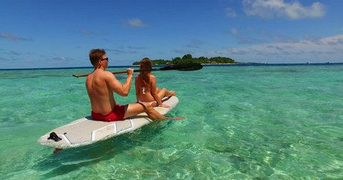 v11316 two 2 people romantic young people couple paddleboard surfboard with drone aerial flying view on a tropical island of white sand beach and blue sky and sea