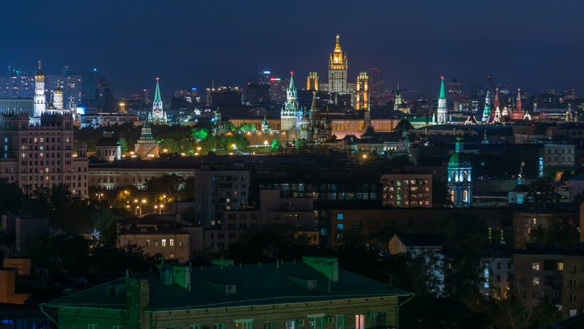 Panoramic aerial view of Moscow timelapse - Kremlin towers, State general store, Stalin skyscraper, residential building at night. Illuminated city from rooftop.