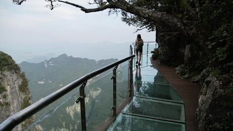 Tourists carefully walk over a glass bridge on Tian Shan National Park in Hunan province, China