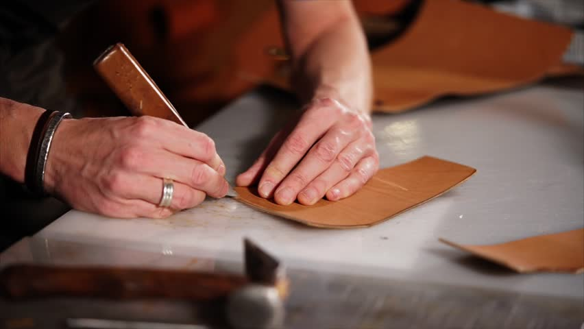close up shot of the master of the hand, who works with leather products, the person holds a sharp knife on patterns to create marks on the product