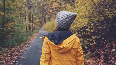 Woman Walking through Autumn Forest. SLOW MOTION 120 FPS, STABILIZED SHOT. Girl in yellow raincoat and knitted hat enjoying fall day outdoors, walking through woodland.  Disconnected concept.