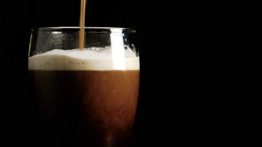 Delicious hand crafted stout, porter or dark beer is poured into a glass