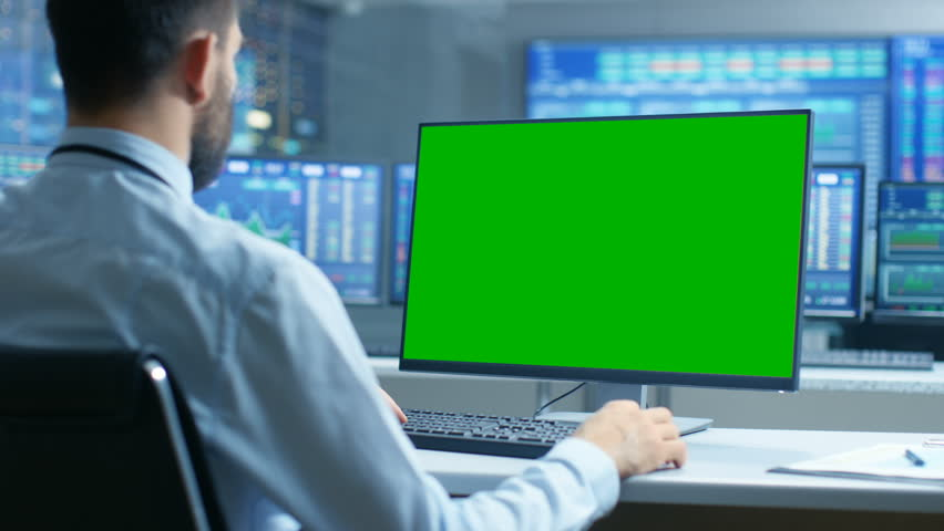 Over the Shoulder View of Stock Market Trader Working on a Computer with Isolated Mock-up Green Screen. In the Background Monitors Show Stock Ticker Numbers and Graphs. Shot on RED EPIC-W 8K Camera.