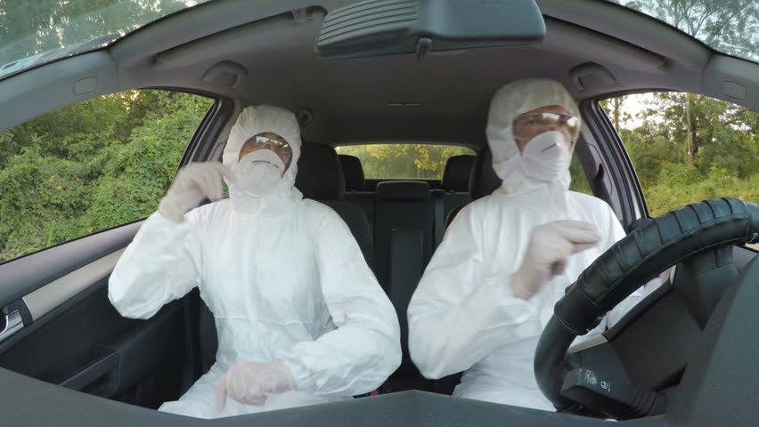 Crazy biohazard scientists technicians in hazmat suits dancing and driving to work in a car