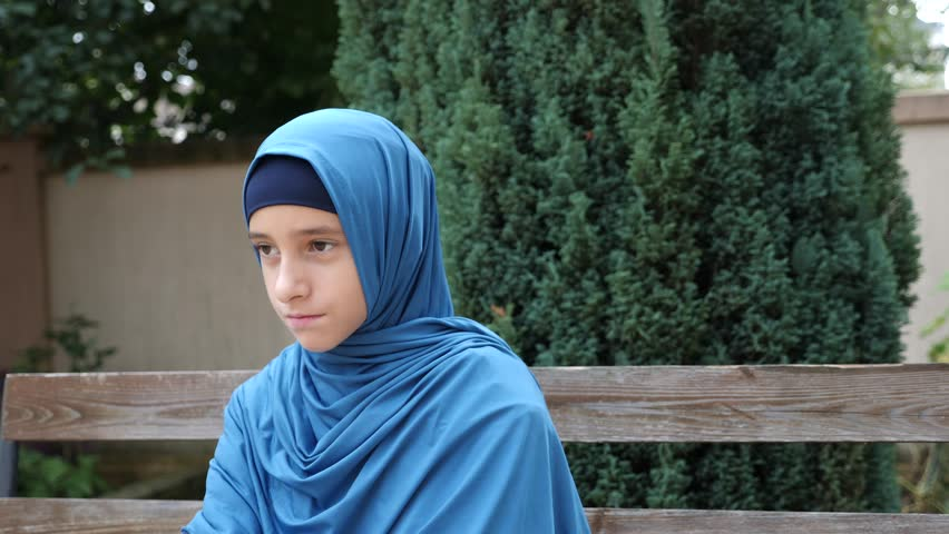 Portrait of a modest girl, a Muslim wearing a hijab looks at the camera, 4k, slow-motion. copy space | Shutterstock HD Video #32333386