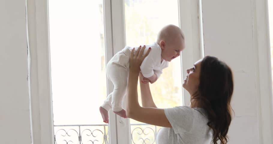 Happy smiling mother with baby having fun together on white of the curtains of the window background #32348686