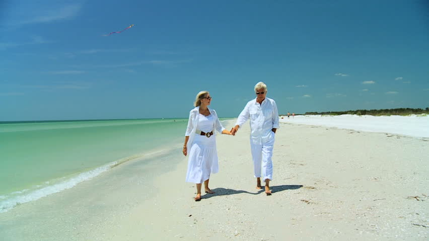 Attractive senior carefree couple walking along the beach barefoot enjoying a fun lifestyle