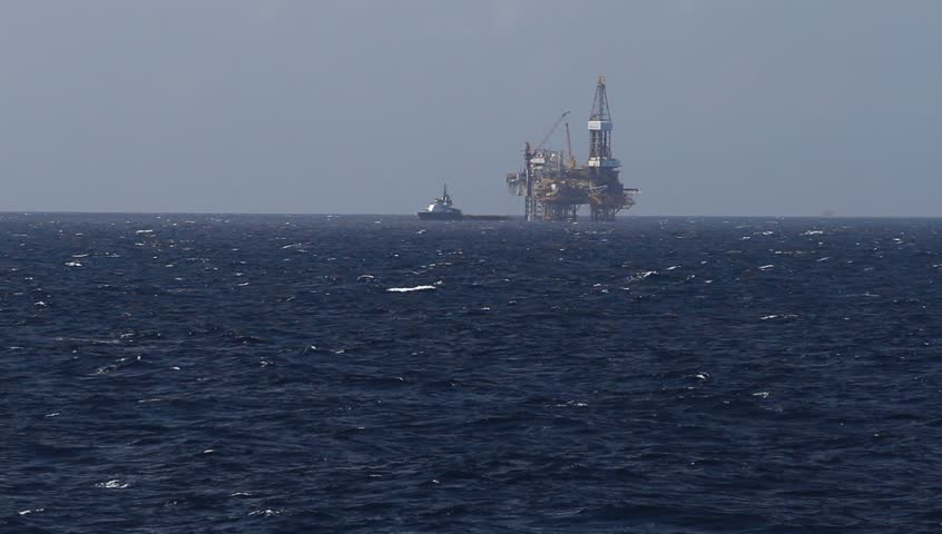 Offshore Jack up drilling rig and crew boat in the middle of the ocean on windy day
