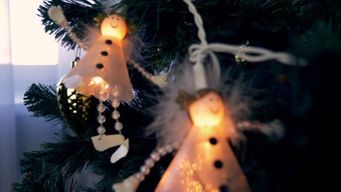 White Angels hange on christmas tree. Cristmas eve and New year festive. Close up dolly shot of lantern with angels. Decor of firtree. Fairy lights Angels. Christmas tree light spruce.