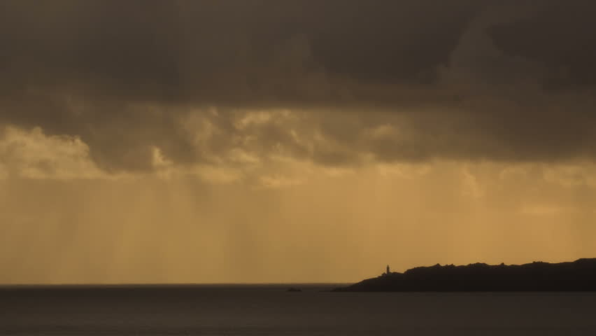 Lighthouse on headland. A very dramatic moody and rainy sky passes over a lighthouse, in Devon, UK