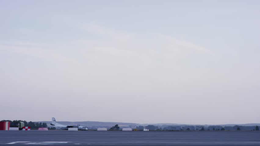 Airport, the plane on takeoff, landscape. Passengers airplane landing to airport runway in beautiful sunset light. White passenger plane is landing away from airport