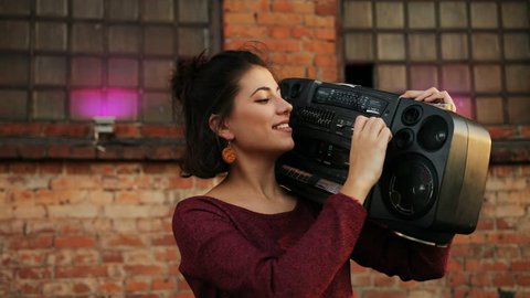 Close up of young pretty woman holding a boombox on her shoulder at the rooftop party. The brick wall background. Urban space. Outside. Portrait