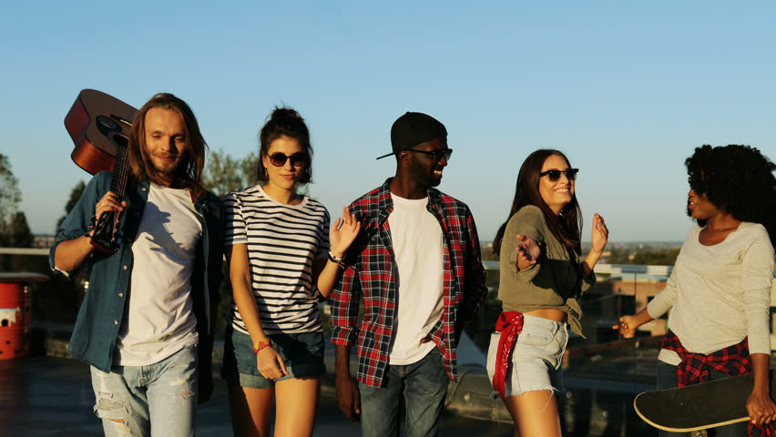Group of young friends with guitar walking and having fun at the rooftop party. The blue sky background. Outside. Multiethnic   Shutterstock HD Video #32392456