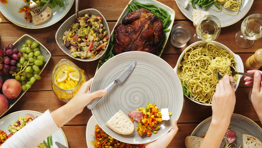 Eating and leisure concept - people having dinner and serving pasta at table with food | Shutterstock HD Video #32420206