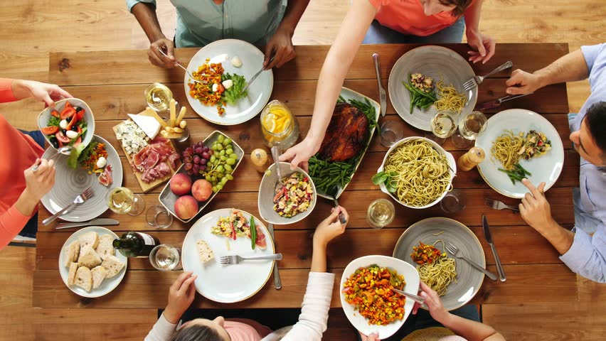 Eating and leisure concept - group of people having dinner at table with food