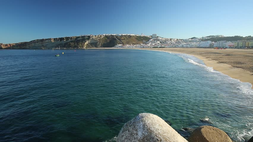 Traditional fishing boat in the calm waters in front of main beach of Nazare in Central Portugal. The high cliffs of Nazare cityscape on background.