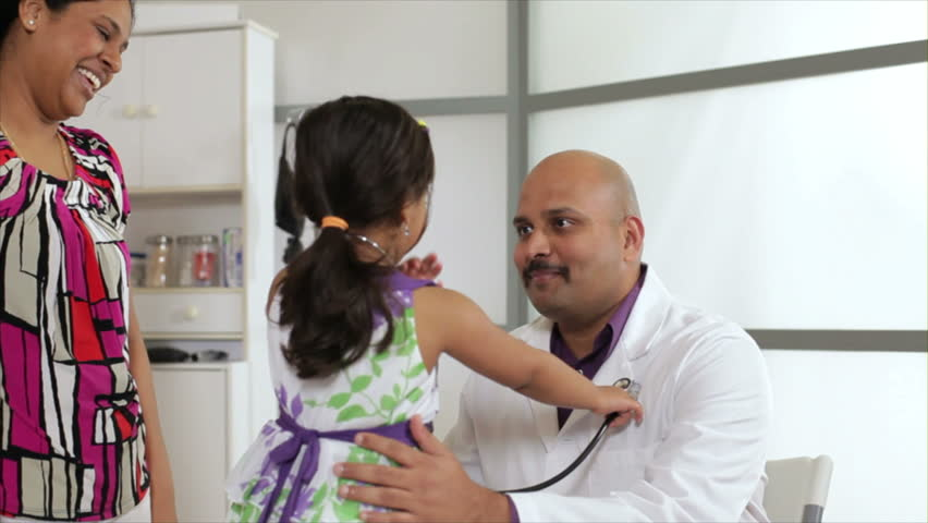 A kind Indian pediatrician allows a little patient with her mother by her side to use the stethoscope to pretend she is the doctor.