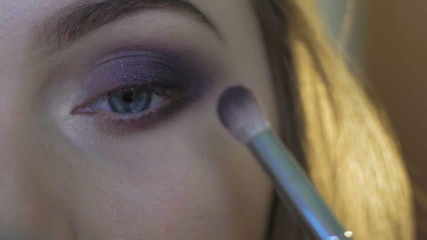 Pretty girl applying eye makeup with shadows. Close up
