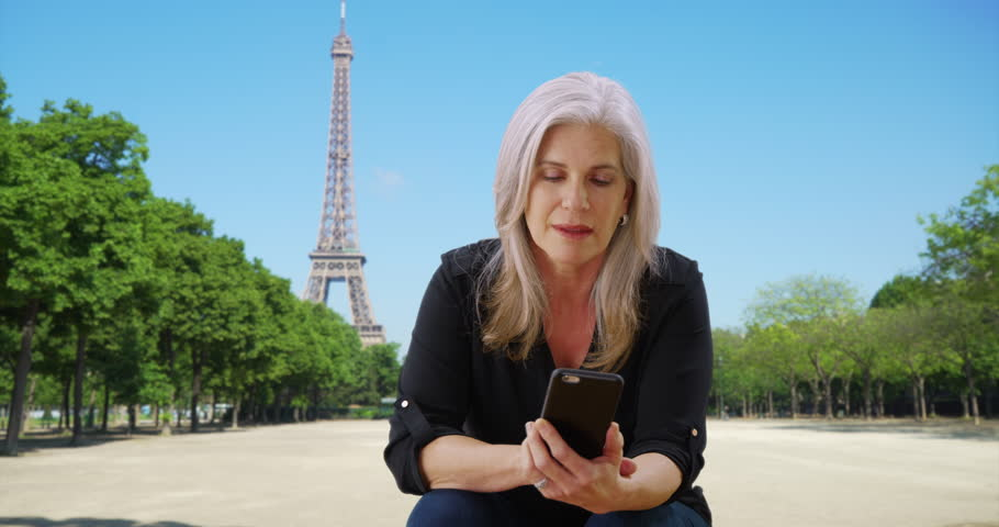 Happy mature woman on vacation in France checks her phone near the Eiffel Tower. Elderly Caucasian female in Paris uses her smartphone by the Eiffel Tower. 4k | Shutterstock HD Video #32500696