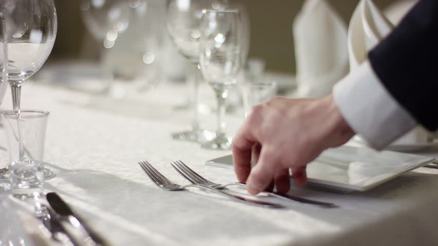 View of waiter hand preparing table for celebration at banquet hall
