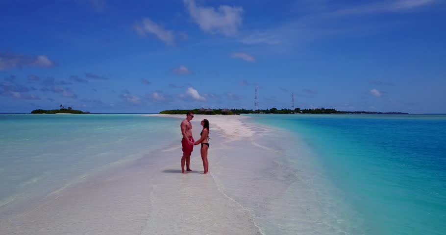 v15459 two 2 people together having fun man and woman together a romantic young couple sunbathing on a tropical island of white sand beach and blue sky and sea
