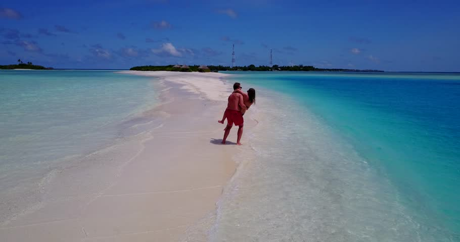 v15456 two 2 people together having fun man and woman together a romantic young couple sunbathing on a tropical island of white sand beach and blue sky and sea