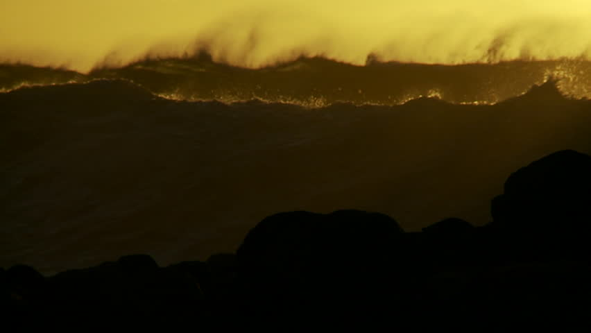 HAWAII, USA, 2012 Large orange and black waves as they crest and break in slow motion at sunset.