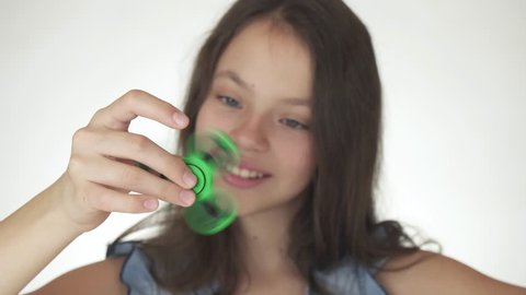 Beautiful cheerful teen girl playing with green fidget spinner on a white background stock footage video