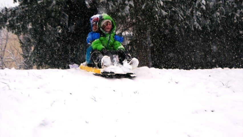 Little girl and boy enjoy a sled ride. Children play outdoors in the snow during a snowfall