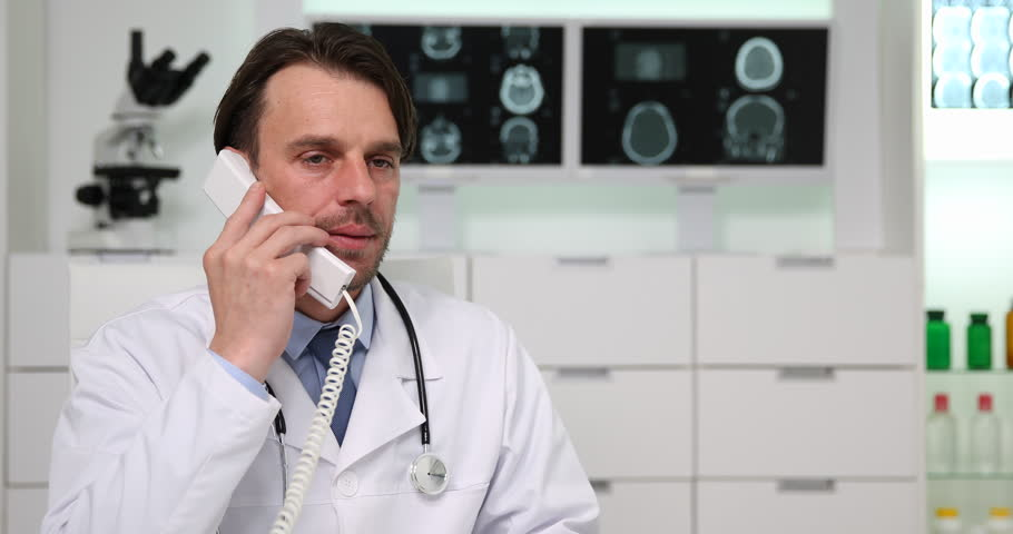 Clinician Doctor Man Talking Landline Phone Receiving Bad News in Cabinet Office