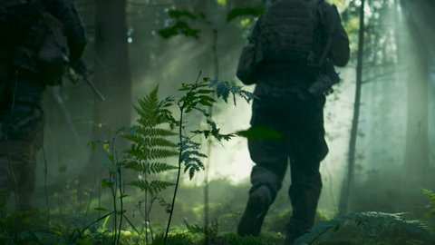 Fully Equipped Soldiers Wearing Camouflage Uniform Attacking Enemy, Rifles Ready to Shoot. Military Operation in Action, Squad Running in Formation Through Dense Smokey Forest. Slow Motion. 4K UHD.