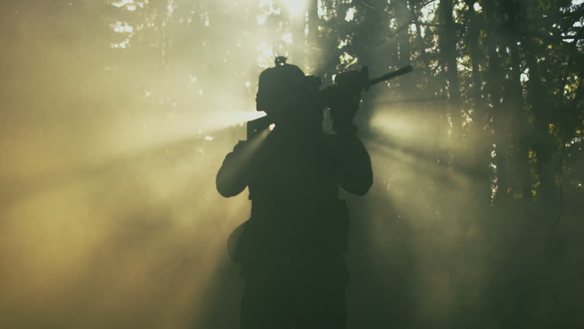 Silhouette of the Fully Equipped Soldier Moving Through Smokey Forest with Rifle Ready To Shoot. Reconnaissance Military Operation. Shot on RED EPIC-W 8K Helium Cinema Camera.
