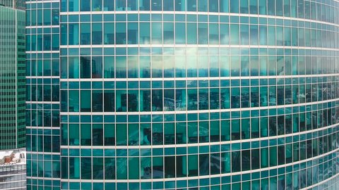 A zooming out shot on business building reflective glass walls.