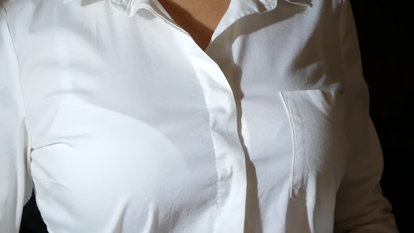 close-up, details. a woman unfastens the top button on her white shirt, removes it.