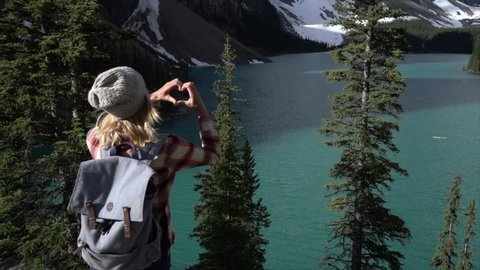 Slow motion shot of young woman standing looking at stunning mountain lake views makes a heart shape frame using her fingers. Woman loving nature at Moraine lake, Banff, Alberta, Canada