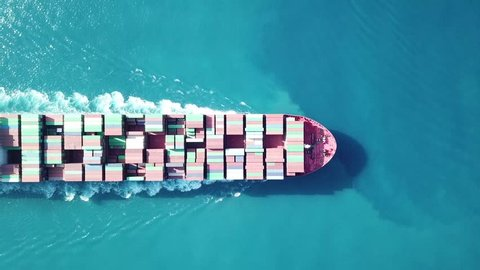 Huge large mega ULCV container ship sails on open water fully loaded with containers and cargo - aerial 4k view