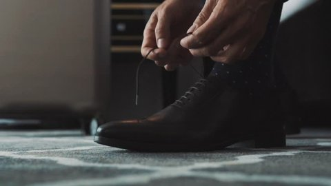 Unrecognizable businessman dressing up in a hotel room. Man tying his shoelaces. Close up. Slow motion.