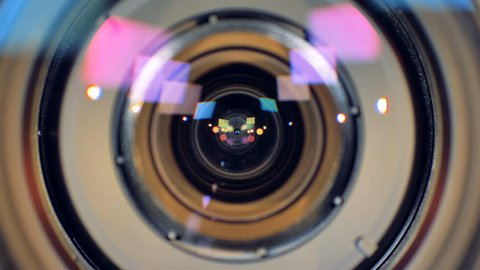 A macro view on a working video camera lens with inner rings seen inside.
