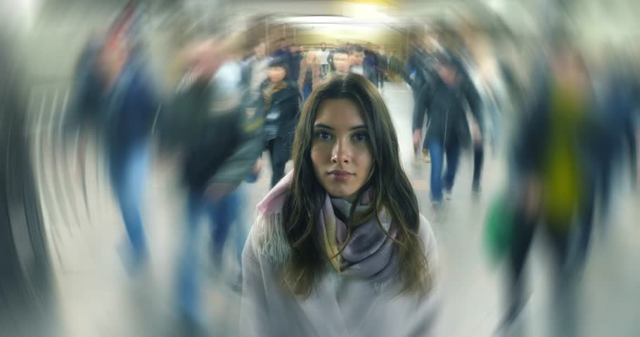Beautiful young woman standing alone in moving crowd, looking at camera. 4K UHD timelapse.