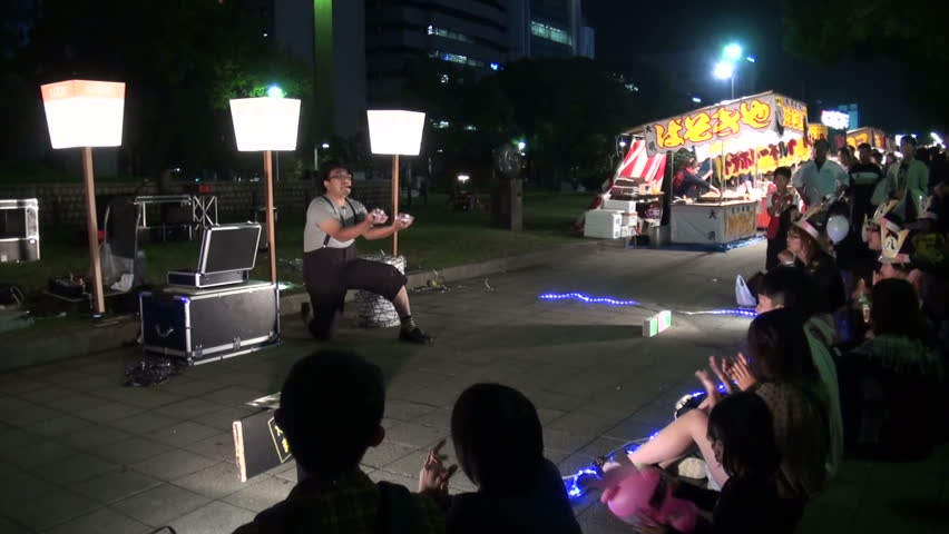 NAGOYA, JAPAN - 20 OCTOBER 2012: A 'magician' is performing on the streets with a small audience of kids and their parents in Nagoya, Japan
