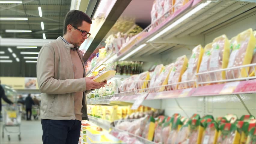 The adult man is in the mall, the person chooses the products in the supermarket, he takes out the chicken from the rack and looks at the bird | Shutterstock HD Video #32718847