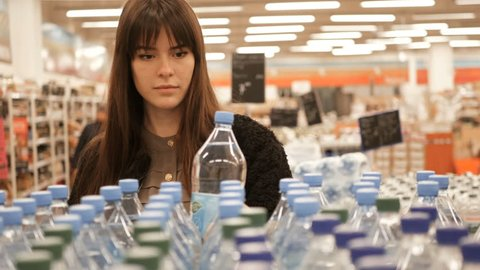 Woman choosing a bottle of mineral water in the store