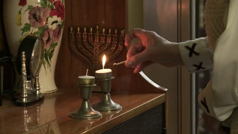 Lighting Hanukkah Candles. Close Up.
