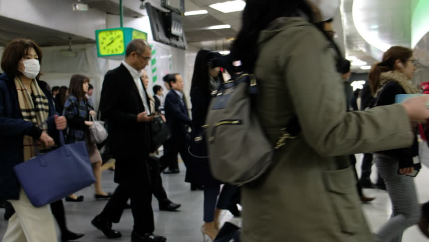 TOKYO, JAPAN - NOVEMBER 10TH 2017. Commuters rushing through ticket gates in Shinjuku Station train platform. Panning shot. #32762266