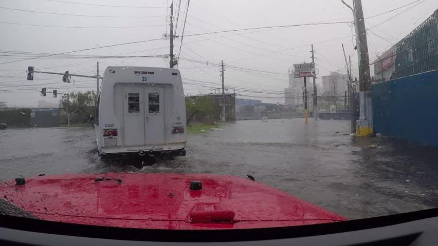 San Juan, Puerto Rico - October 03, 2017: Cars drive through flooded road section in San Juan city, Puerto Rico