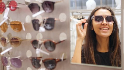 Young Mixed Race Hipster Girl Trying Sunglasses and Fooling Around in Shopping Mall. Fun Fashion Look 4K Slow Motion.
