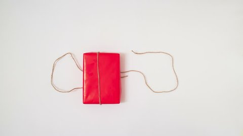 stop motion of present packing in red wrapping paper on white background