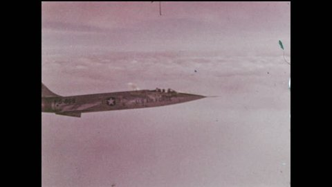 1970s: Lockheed F-104 Starfighter USAF supersonic jet flies above thick clouds into night sky of twilight, tilts wings and elevates altitude.